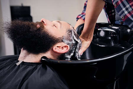 shampooing: Close up image of female hairdresser washing bearded mens hair before haircut in a saloon.