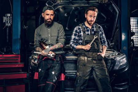Two bearded tattooed mechanics with nut key near the car with open engine hood in a workshop.