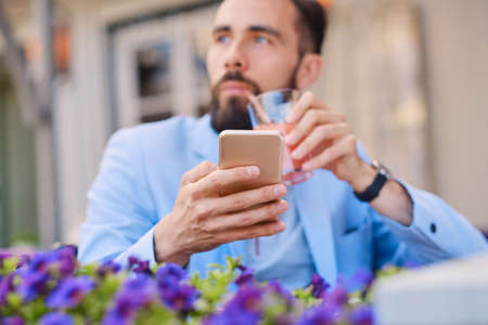 throttle: Stylish bearded male in a blue jacket using smartphone. Stock Photo