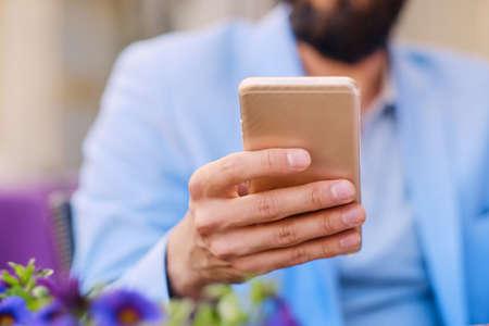 Stylový vousatý muž v modrém saku pomocí smartphonu.