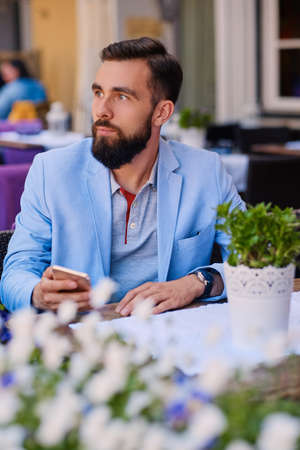Stylish bearded male in a blue jacket using smartphone at the table in a cafe.