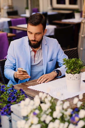 hairdresser: Stylish bearded male in a blue jacket using smartphone at the table in a cafe.