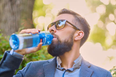 Bearded hipster male in sunglasses, drinks mineral water.