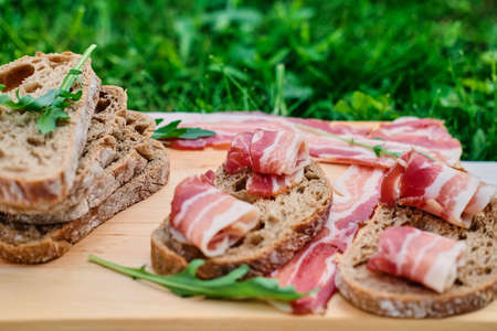 Bread with gourmet meat on a wooden desk over green lawn background. Zdjęcie Seryjne