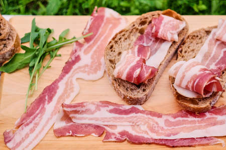 Bread with gourmet meat on a wooden desk over green lawn background. Stock Photo