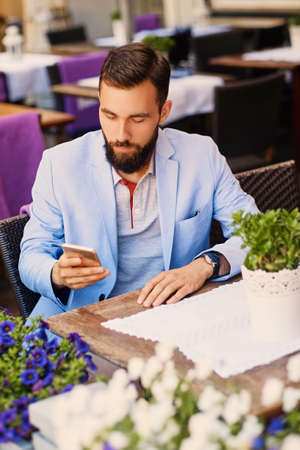 throttle: Stylish bearded male in a blue jacket using smartphone at the table in a cafe.