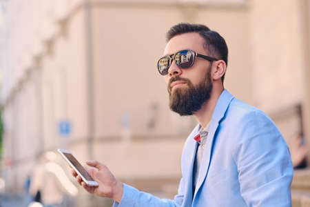 Portrait of bearded male in sunglasses using a smartphone.