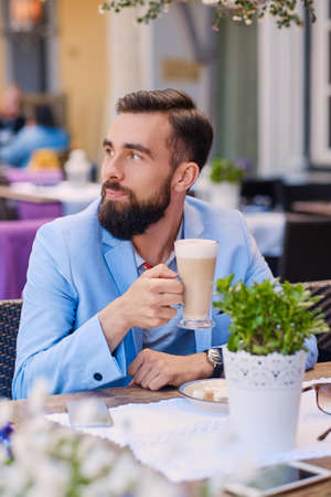 Bearded male drinks coffee at a cafe.