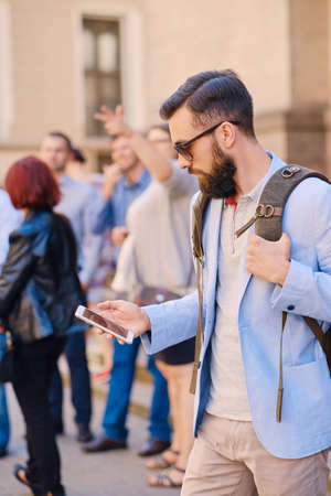 hairdresser: Stylish bearded male in a blue jacket using smartphone. Stock Photo