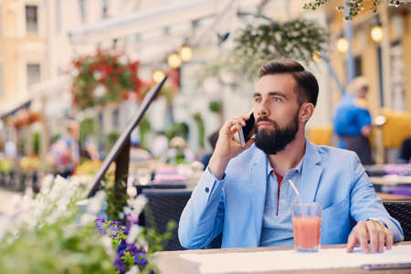 cool gadget: Stylish bearded male in a blue jacket talks by smart phone in a cafe.