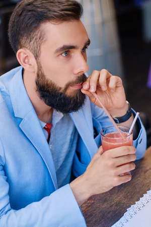 Bearded male drinks, fresh juice at a cafe.