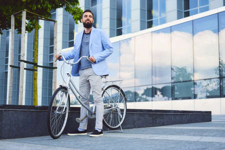 Luxury bearded male in a sunglasses on a bicycle in a downtown. Stock Photo