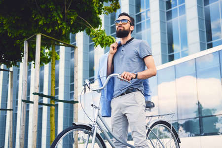 hairdresser: Luxury bearded male in a sunglasses on a bicycle in a downtown. Stock Photo