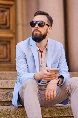 The stylish bearded male sits on a step and using smartphone.