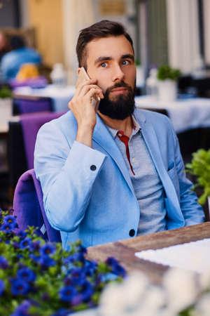 Stylový vousatý muž v modrém saku pomocí smartphonu u stolu v kavárně. Reklamní fotografie