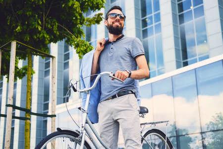 Luxusní vousatý muž ve slunečních brýlích na kole v centru města.