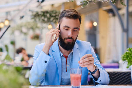 Stylish bearded male in a blue jacket talks by smart phone in a cafe.