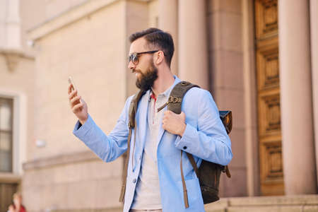Stylish bearded male in a blue jacket using smartphone. Stock Photo