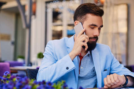 Portrait of fashionable bearded male in a blue jacket talks by smartphone.
