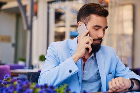 throttle: Portrait of fashionable bearded male in a blue jacket talks by smartphone.