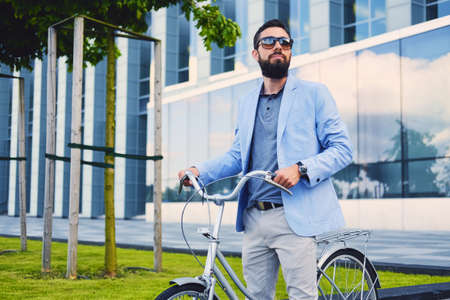 Luxury bearded male in a sunglasses on a bicycle in a downtown. Reklamní fotografie