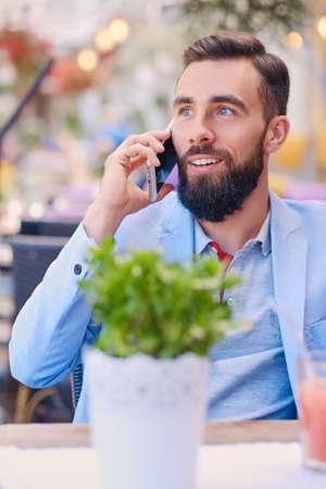 Portrét módní vousatého muže v modré bundě mluví smartphone.