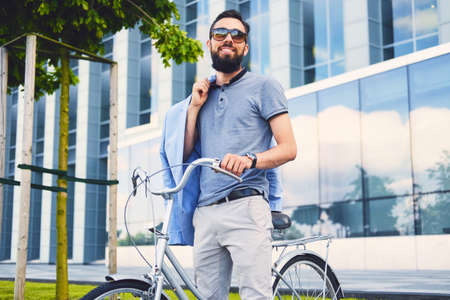 throttle: Luxury bearded male in a sunglasses on a bicycle in a downtown. Stock Photo