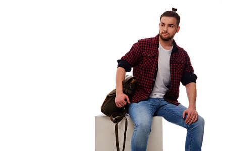 Studio portrait of bearded male dressed in a jeans and fleece shirt with a backpack. Isolated on white background.