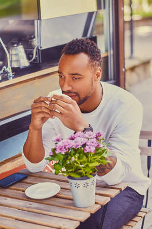 Black man drinks coffee in a cafe on a street.