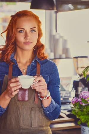 master: Portrait of redhead female barista in a small coffee shop.