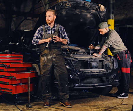 auto repair: Two bearded tattooed mechanics with nut key near the car with open engine hood in a workshop.
