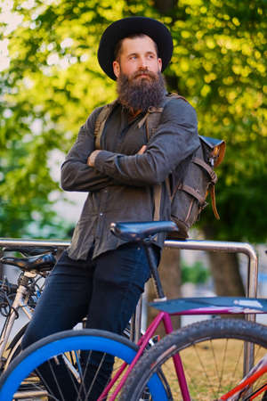 Bearded hipster male with backpack near city bicycle parking. Stock Photo