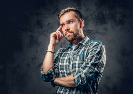 hairdresser: Studio portrait of thoughtful bearded hipster male over grey background. Stock Photo