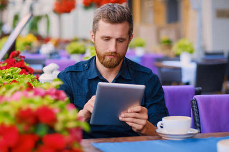 tea hot drink: Casual bearded male drinks coffee and using a tablet PC in a cafe.