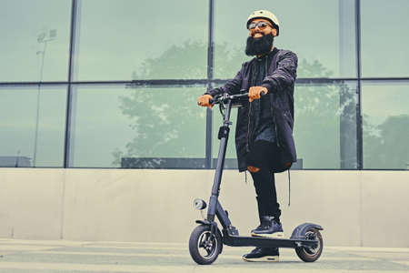 Stylish bearded male in sunglasses posing on electric scooter in over modern building background.