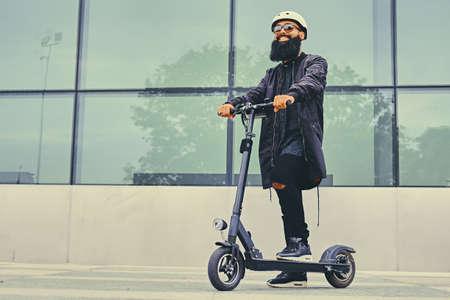 Mâle barbu élégant dans des lunettes de soleil posant sur un scooter électrique sur un fond de construction moderne. Banque d'images - 83990056