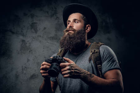 jewish: Studio portrait of bearded tattooed photographer holds compact camera over grey background.