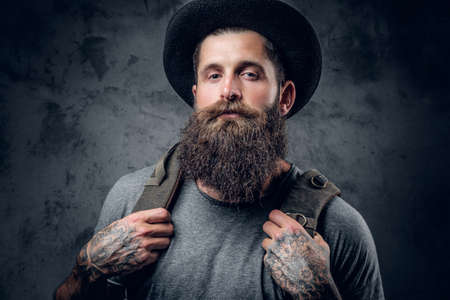 Bearded tattooed male in a hat with a backpack over grey background. Reklamní fotografie
