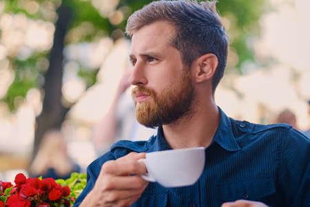 Portrét vousatý zrzka neformální muž pije kávu v kavárně na ulici. Reklamní fotografie
