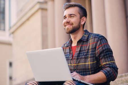 A casual bearded male dressed in a jeans and fleece shirt sits on a step and using a laptop.