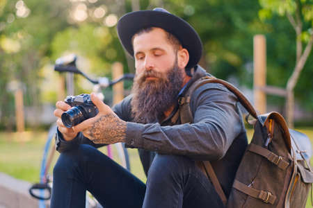Portrait of casual tattooed, bearded street photographer sits on a step. Stock Photo
