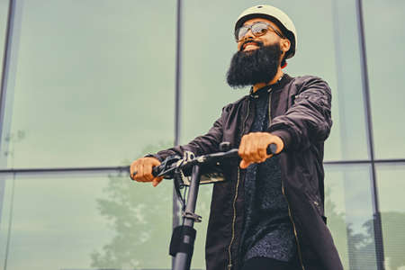 throttle: Stylish bearded male in sunglasses posing on electric scooter in over modern building background.