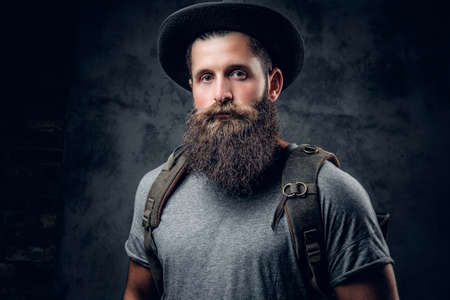 throttle: Bearded tattooed male in a hat with a backpack over grey background. Stock Photo