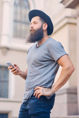 throttle: Portrait of a tattooed, bearded male in a hat holds a smartphone. Stock Photo