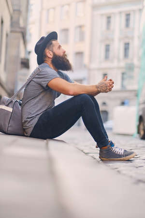 throttle: The full body image of casual bearded hipster sits on a step on a street.