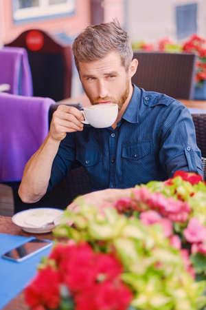 Portrait of bearded redhead casual man drinks coffee in a cafe on a street. Reklamní fotografie