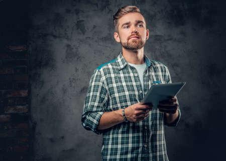 Bearded male in a fleece shirt holds tablet PC over grey background. Reklamní fotografie