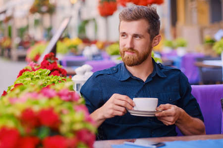 Portrait of bearded redhead casual man drinks coffee in a cafe on a street. Stock Photo