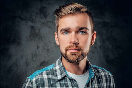 Studio portrait of a blue eyed, bearded hipster male over grey background.