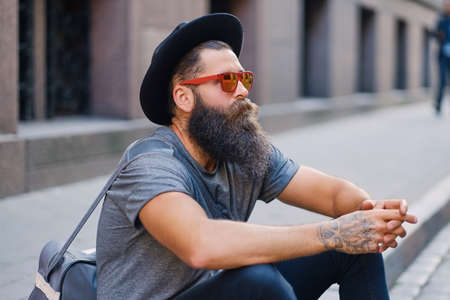 Casual bearded hipster male in sunglasses and hat sits on a step on a street.